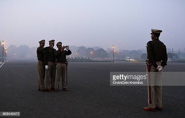 An Indian Army personnel has his picture taken by colleagues ahead of the rehearsal for the forthcoming Republic Day parade on a foggy winter morning...