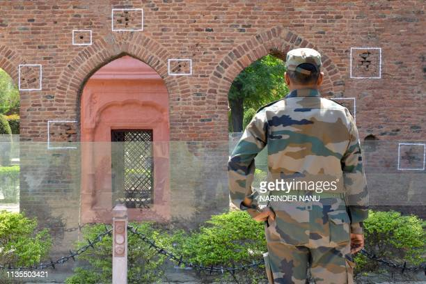 An Indian army personnel looks at the bullet marks on a wall near the Jallianwala Bagh Martyrs' Memorial ahead of the 100th anniversary of the...