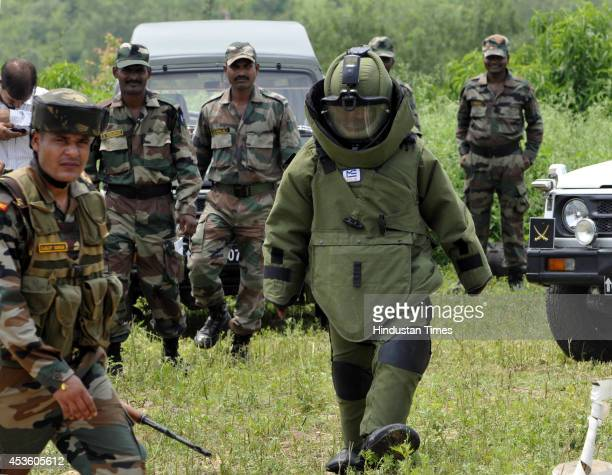 An Indian army personnel of bomb disposal squad walks towards disposing a unexploded explosives and shells at Akhnoor sub division on August 14 2014...
