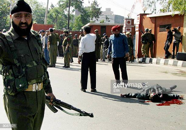 An Indian army soldier and police bombsquad officers ask others to move back from the body of an alleged militant in case it is rigged with...