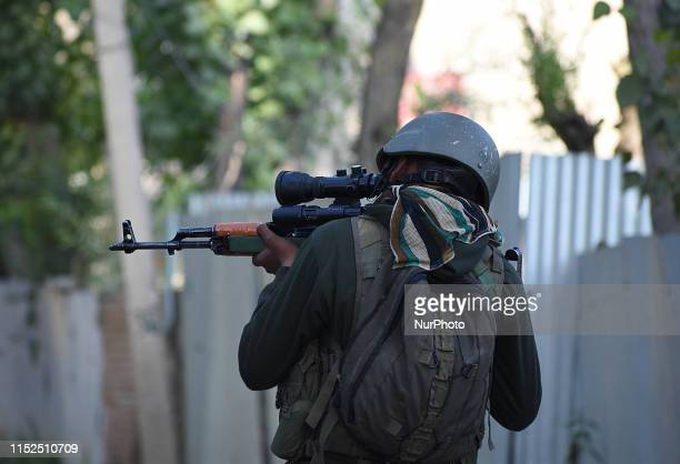 An Indian army soldier checks his rifle near the gunbattle site in Checkpora area of Budgam district on June 282019One militant was killed when a...