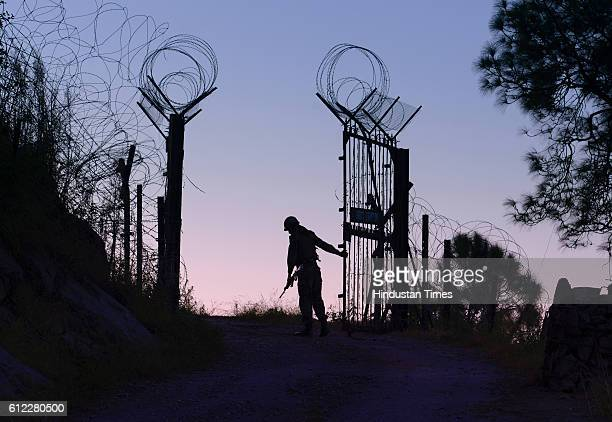 An Indian Army soldier closes the gates on the fence near the LOC separating India and Pakistan on September 29 2015 in Barasingha area near Bhimber...