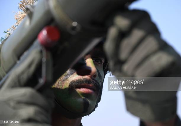 An Indian army soldier displays his combat skills in a demonstration as he carries a rocket launcher during the army Day parade in New Delhi on...