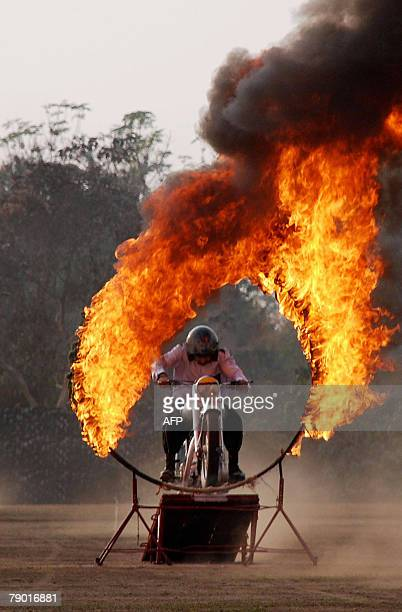 An Indian Army soldier from the famous Dare Devil team rides through a ring of fire on a motorcycle during an exhibition show at Binnaguri cantonment...