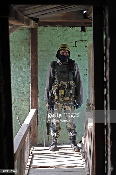 An Indian Army soldier guard on top of a polling station during the second phase of Jammu and Kashmir Assembly elections in Kulgam about 70 km from...