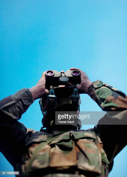 An Indian army soldier look towards they building where the militants are holed up during a gun battle on February 21 2016 in Srinagar the summer...