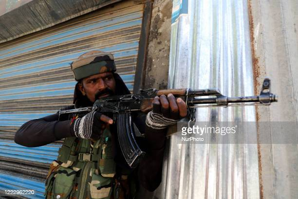 An Indian army soldier looks towards the encounter site in Sopore town of District baramulla Jammu and Kashmir India on 25 June 2020