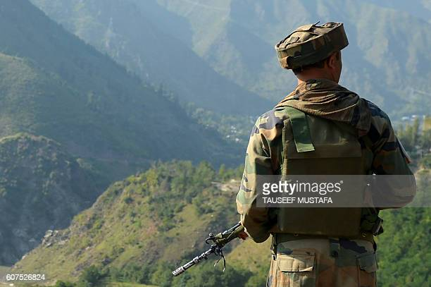 An Indian army soldier looks towards the site of a gunbattle between Indian army soldiers and rebels inside an army brigade headquarters near the...