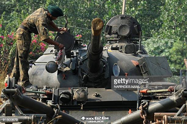 An Indian Army soldier of the 15th Infantry Division cleans the turret of a T55 tank during the celebration of 46th Raising Day Exhibition and Fair...