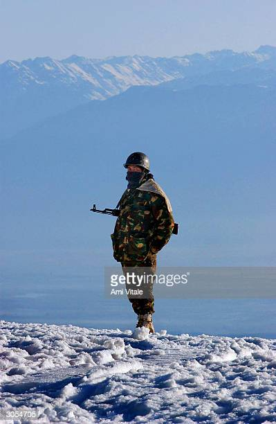 An Indian Army soldier patrols near the ski slopes where India's national winter ski championships were held in Kongdoori March 7 2004 in Kashmir...