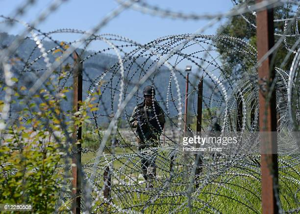 An Indian Army soldier patrols on the fence near the IndiaPakistan LOC on September 30 2015 in ChakandaBagh area near Poonch India The term Line of...