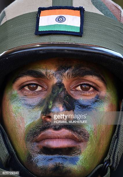 An Indian Army soldier sits with soldiers of the People's Liberation Army of China after participating in an antiterror drill during the Sixth...