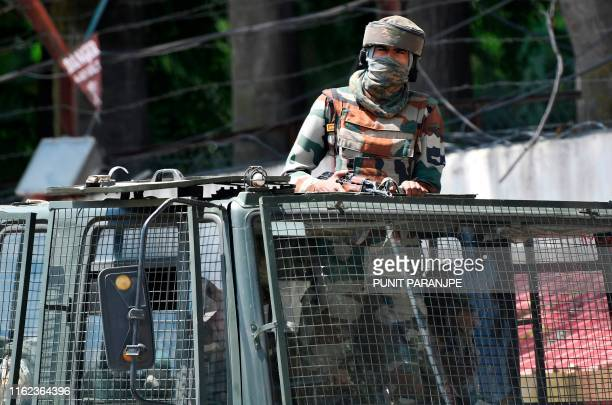 An Indian army soldier stands alert in a truck while travelling in a convoy in Srinagar on August 18 2019 Thousands of people have been detained in...