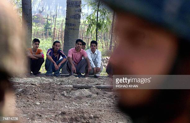 An Indian Army soldier stands guard as Kashmiri Muslim youths are detained for questioning after an explosion on the outskirts of Srinagar 24 June...