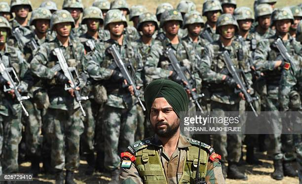 An Indian Army soldier stands in front of a group of People's Liberation Army of China soldiers as they line up after participating in an antiterror...