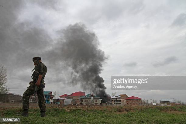 An Indian army soldier walks as the smoke from the blasted house is seen in which suspected rebel was believed to be trapped during an encounter in...