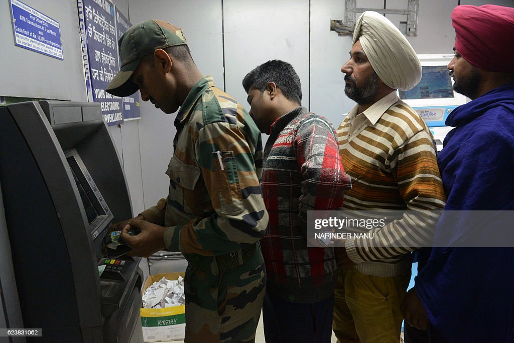 An Indian army soldier withdraws money at the front of a queue from an ATM in Amritsar on November 17 2016 Long queues formed outside banks in India..