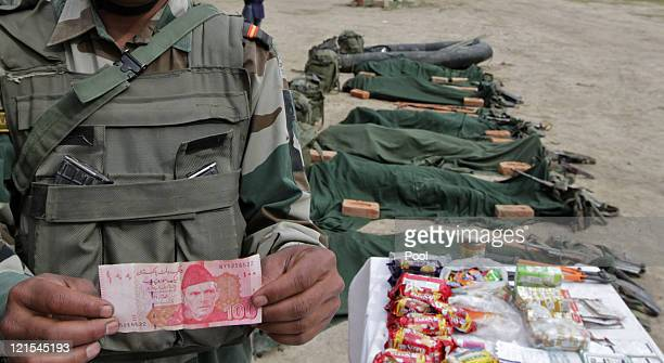An Indian Army soldiers displays a Pakistani note recovered from the body of one of the suspected militants killed by the Indian Army on August 20...