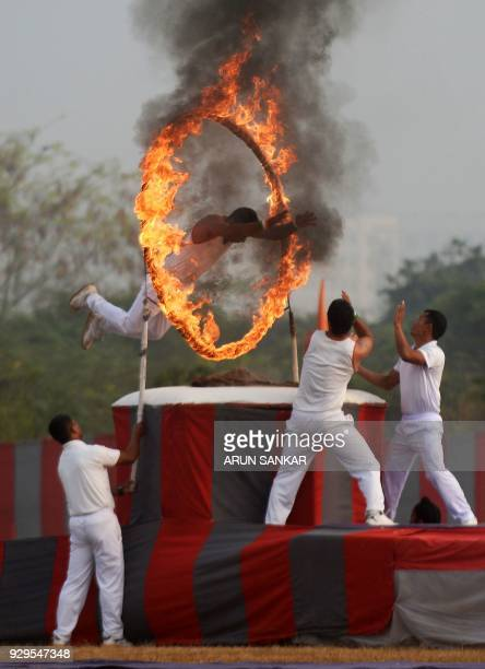 An Indian army training cadet jumps through a ring of fire as he performs a gymnastic drill during a combined display at an officer training academy...