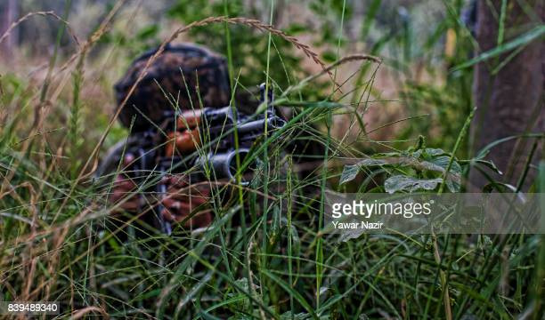An Indian army trooper aims his rifle in an apple orchard towards the camp where rebels are fighting with their comrades on August 26 2017 in Pulwama...