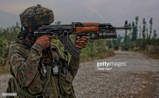 An Indian army trooper stands guard on the road leading towards their camp where rebels are fighting with their comrades on August 26 2017 in Pulwama...