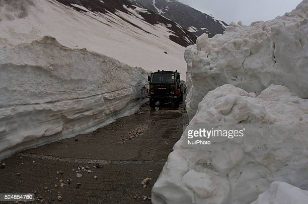 An Indian army vehicle passes through the snowcleared SrinagarLeh highway on a treacherous pass after it was reopened by authorities on May 13 2015...