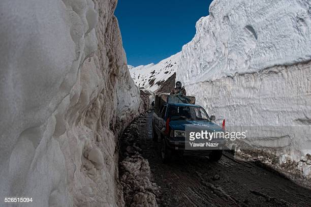 An Indian army vehicle passes through the snowcleared SrinagarLeh highway on April 30 2016 in Zojila 108 km east of Srinagar the summer capital of...