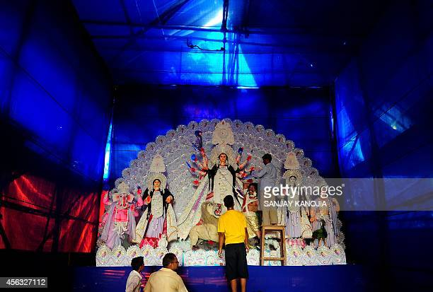 An Indian artisan give the final touches to a Durga puja 'pandal' ahead of the Dussehra festival in Allahabad on September 29 2014 Dussehra is a...