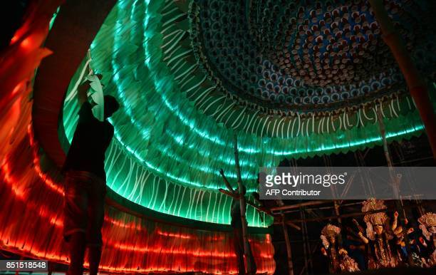 An Indian artisan gives final touches to a Durga puja 'pandal' ahead of the 'Dussehra' festival in Allahabad on September 22 2017 'Dussehra' is a...
