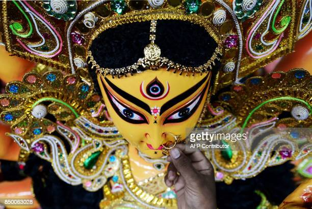 TOPSHOT An Indian artisan puts a nose ring as he gives finishing touches on a clay idol of the Hindu Goddess Durga at his workshop in Chennai on...