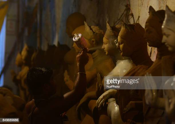 An indian artisan sprays color to give a decorative touch to the clay idols of Indian hindu Goddess Durga in a workshop ahead of Navratri and Durga...