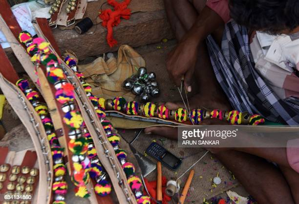 An Indian artisan stitches a decorative necklace for a bull ahead of the Jallikattu bull taming event in the south Indian city of Madurai on February...