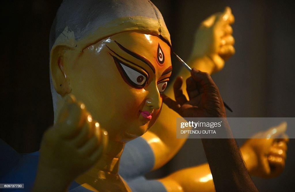 An Indian artisan works on semifinished clay idols of Hindu goddess Durga inside his workshop in Kumartoli the idol makers' village of Siliguri on...