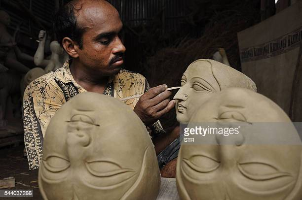 An Indian artisan works on the clay face of an idol of hindu goddess Durga at a studio in Agartala capital of northeastern state of Tripura on July 1...