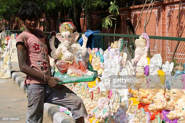 An Indian Artisans work on clay idols of Lord Ganesha ahead of the festival of Ganesha Chaturthi at roadside workshop in Jaipur 10 Sept2015