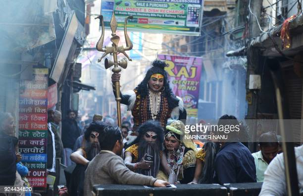 An Indian artist dressed as Hindu god Lord Shiva takes part in a procession ahead of the Holi festival in Amritsar on February 26 2018 Holi the...