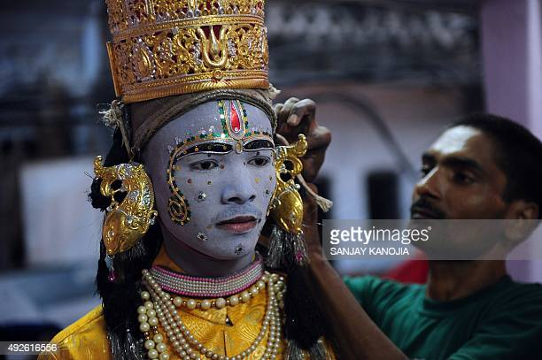 An Indian artist dressed as Hindu god Rama has his costume adjusted ahead of a religious procession during the Dussehra festival in Allahabad on...