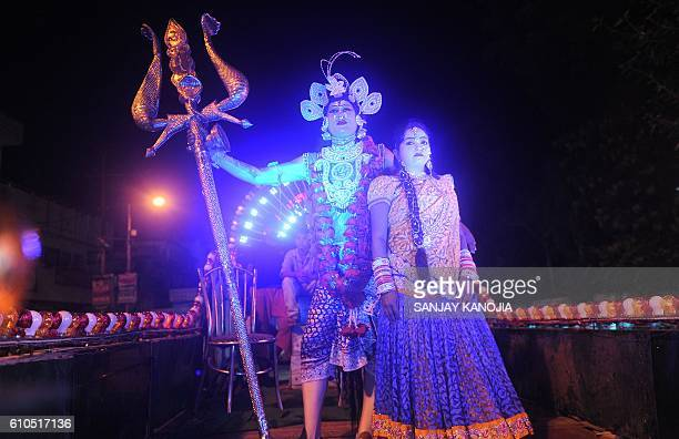 TOPSHOT An Indian artist dressed as Hindu god Shiva performs on a chariot as he participates in a religious procession 'Ravan ki Barat' held to mark...