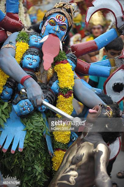 An Indian artist dressed as Hindu Goddess MahaKali performs while in a trance during the final procession of the elevenday traditional festival of...