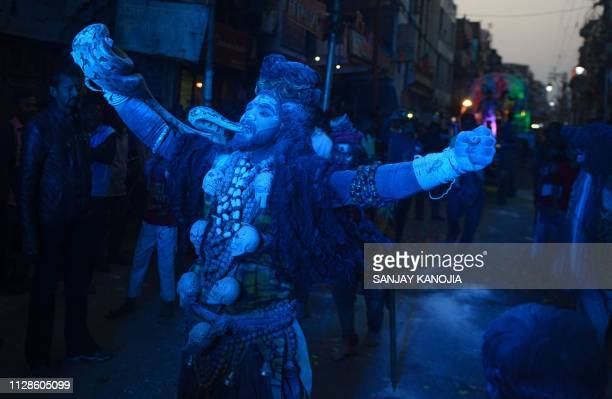 TOPSHOT An Indian artist dressed as Hindu Lord Shiva performs during a procession on the occasion of 'Maha Shivaratri' festival in Allahabad on March...