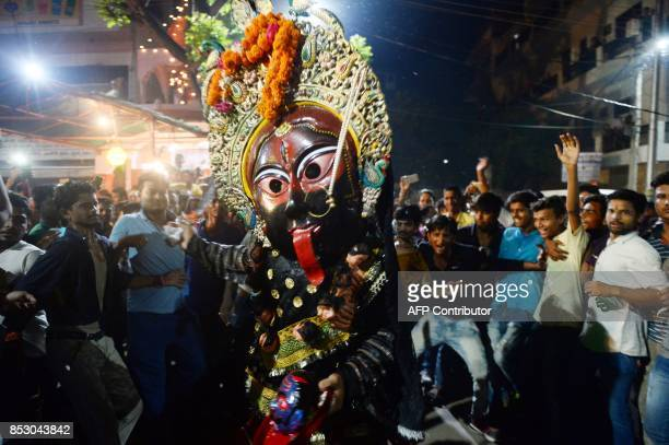 An Indian artist dressed as the Hindu Goddess Kali performs the traditional 'Kali Swang' organised annually by the Daraganj Ramleela committee during...