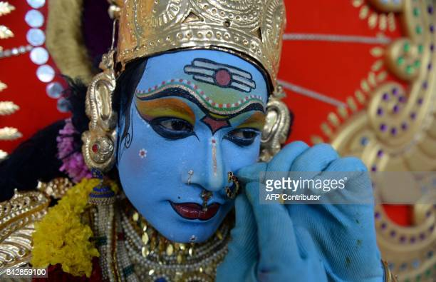 An Indian artist dresses as a Hindu god before performing in the 'Kummati Kali' as part of the annual Onam festival celebrations in the Thrissur...