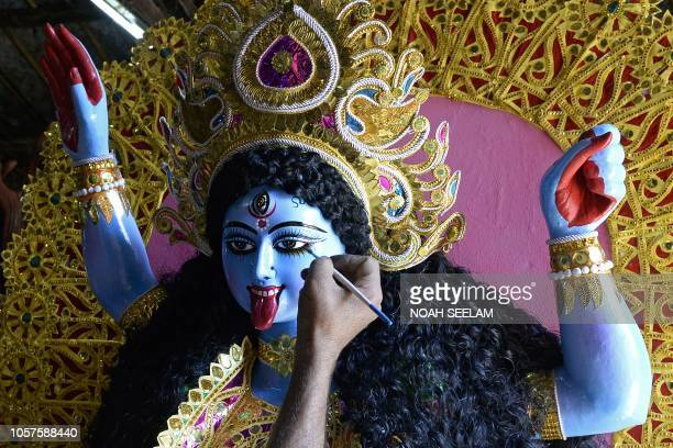 An Indian artist gives final touches to an idol of the Hindu Goddess Kali at a workshop ahead of the Diwali festival in Hyderabad on November 5 2018...