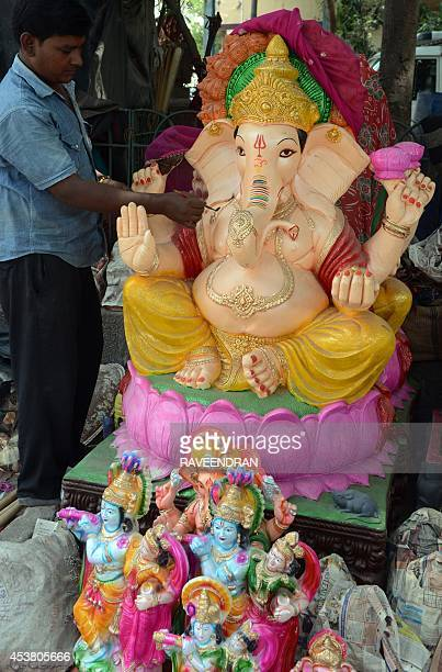 An Indian artist paints a statue of the elephantheaded Hindu god Lord Ganesh at a roadside workshop in New Delhi on August 19 2014 The statues are...