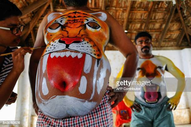 An Indian artist paints the head of a tiger on the belly of a man in preparation for the Puli Kali dance during the Onam festival in Thrissur...