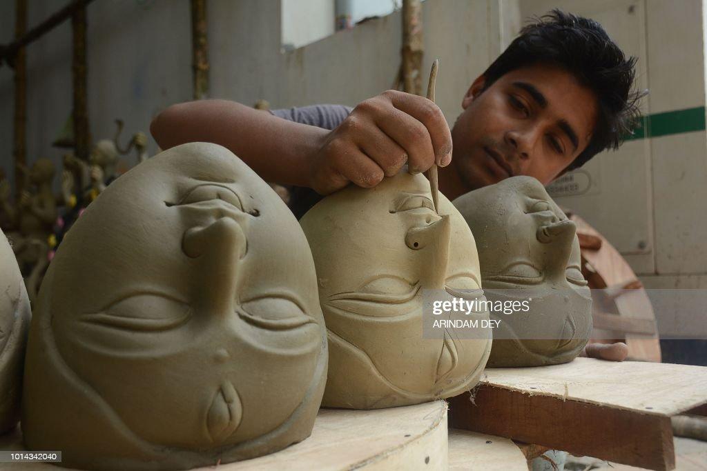 An Indian artist prepares a clay idol of goddesses Durga ahead of the Durga Puja festival inside of a studio in Agartala the capital of northeastern...