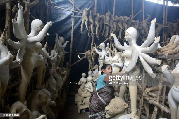 An Indian artist prepares a clay idol of Hindu deity Durga at a workship ahead of the Durga Puja festival in Agartala the capital of northeastern...