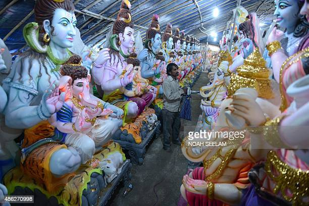 An Indian artist uses a machine to dry statues of the Hindu God Lord Ganesh at a workshop on September 1 ahead of the forthcoming Ganesh Chaturthi...