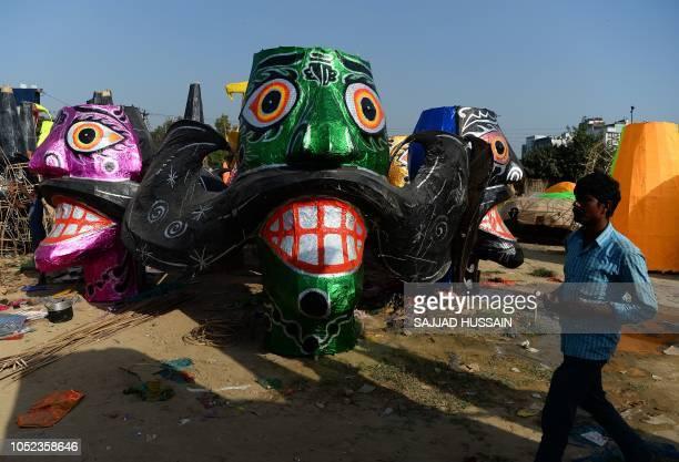 An Indian artist walks near effigies of the demon King Ravana ahead of Dussehra festival celebrations in New Delhi on October 17 2018 On the last day...