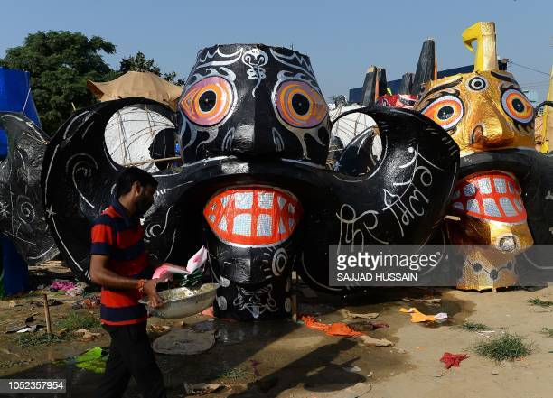 An Indian artist walks near the effigies of the demon King Ravana ahead of Dussehra festival celebrations in New Delhi on October 17 2018 On the last...